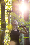 Young blonde woman working out with dumbbells outside in foreste Royalty Free Stock Photography