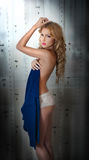 Young blonde woman wrapped in blue towel posing relaxed. Beautiful young woman with a towel around her body after bath. Side view Stock Image