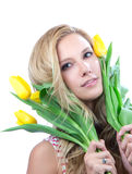 Young blonde woman with yellow spring tulips Royalty Free Stock Photo