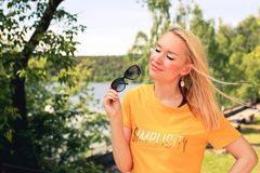 Young blonde woman in yellow t-shirt with sunglassen in her hand enjoing summer sun in the park royalty free stock photo
