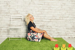 Young blonde women in dress sitting on the grass Royalty Free Stock Image