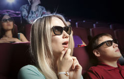 Young blonde women sitting at the cinema, watching a film Royalty Free Stock Photo
