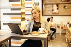 Blonde woman using laptop in internet cafe Royalty Free Stock Photography