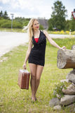 Young blonde women waiting any car on the road. Young blonde woman with suitcase waiting any car on the road Royalty Free Stock Photography