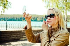 Cute woman looks in small mirror on the street and corrects make up. Blurred natural background royalty free stock photos
