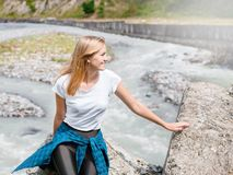 Young woman sitting on rock in fast mountain river and splashing on summer or early autumn outdoor copy space background. Young blondhair woman posing by a stock photos