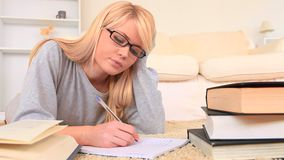 Young blondhaired woman revising for an examination Royalty Free Stock Photos