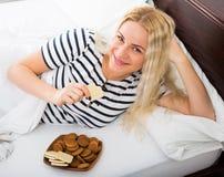 Young blondie enjoying sweet cookies in bed Stock Image
