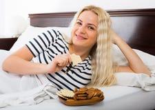 Young blondie enjoying sweet cookies in bed Stock Photos