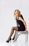 Young blondie girl. In black dress and stockings posing sitting on the chair Stock Photo
