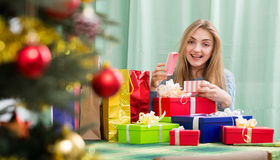 Young blondie opening box with Christmas gift indoors Royalty Free Stock Photo