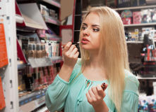 Young blondie selecting lip gloss Royalty Free Stock Image
