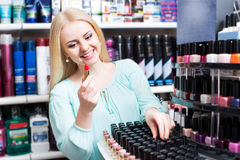 Young blondie selecting lipstick Stock Image