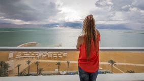 Young blondie woman balcony sea view. Young blondie woman back view standing balcony above sea beach, Ein Bokek, Dead Sea, Israel Royalty Free Stock Photos