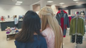 Young blondie woman shows her friend image on smartphone. Shopping stock video footage