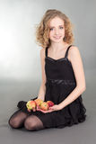 Young blondie woman sitting with apples Stock Images