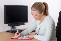 Young blondie woman writing in notebook Royalty Free Stock Photography