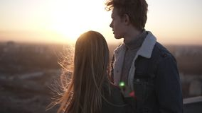Young blondy boy and her long haired girlfriend are standing on the roog during the sunrise embracing. Enjoying the. Togetherness, caressing each other and stock video