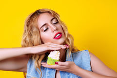 Young blondy model is enjoyment with delicious cupcake over yellow background. Royalty Free Stock Image
