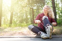 Young blonge woman ties shoelaces on her roller boots stock images