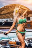 Young Blonie Sexy Lady Is Standing Near The Pool And Holding Mobile Phone While Listening To Music With Yellow. Headphones. She Is Dressed In A Bright stock images