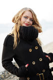 Young blound woman in black scarf and overcoat Stock Photos