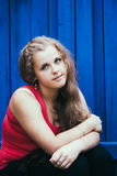 Young Blue-Eyed Girl. Casual Young Blue-Eyed Girl Sitting Near Blue Wooden Wall Stock Photography