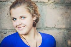 Young blue-eyed girl. Near brick wall Royalty Free Stock Image
