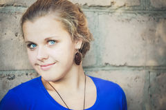 Young Blue-Eyed Girl. Near Brick Wall Stock Photography