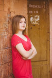 Young blue-eyed girl. Near grunge wall. Her Hands Crossed Stock Photo