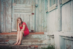 Young blue-eyed girl. Near grunge wooden wall Stock Photo