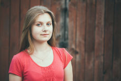Young blue-eyed girl. Near grunge wooden wall Royalty Free Stock Photos