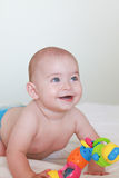 Young Blue Eyed Infant Boy Laying on Bed Laughing Stock Photos