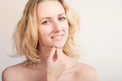 young blue eyed model`s portrait with surgery lines for skin lifting royalty free stock image
