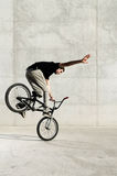 Young BMX bicycle rider. On a grey urban concrete background Stock Photos