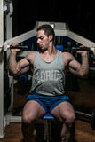 Young body builder doing shoulder press on machine Stock Image