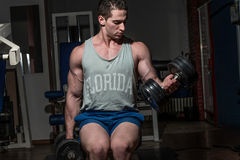 Young bodybuilder doing heavy weight exercise for biceps with du Stock Photo