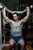 Young bodybuilder doing shoulder press on machine Stock Photography