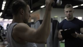 Young bodybuilder is doing wide grip pulldowns exercise with coach in gym. Handsome man trains intensively in modern sports club with instructor. Hardener stock video