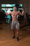 Young Bodybuilder Exercising Biceps On Cable Machine Stock Photo