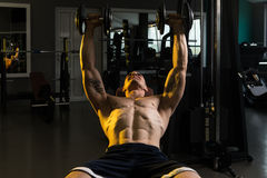 Young Bodybuilder Exercising Chest With Dumbbells Stock Photo