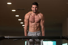 Young Bodybuilder Exercising Triceps Doing Dips on Bar Royalty Free Stock Photos