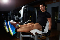 Young bodybuilder flexing legs muscles on gym machine Stock Photography