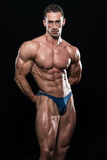 Young Bodybuilder Flexing Muscles Isolate On Black Blackground Stock Photo