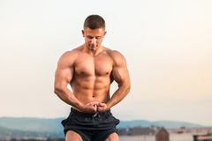 Bodybuilder flexing muscles on a rooftop. Young bodybuilder flexing muscles on a rooftop Royalty Free Stock Images