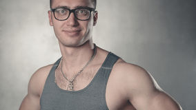 Young bodybuilder in glasses. In the studio Royalty Free Stock Photography