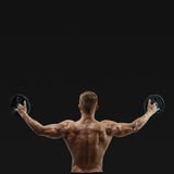 Young bodybuilder lifting weights Royalty Free Stock Images