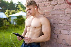 Young bodybuilder man is resting on nature of the tablet in hands and watching movie Royalty Free Stock Image