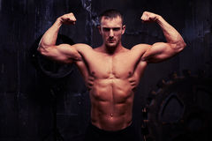 Young bodybuilder with motivated look showing his pumped biceps stock photography