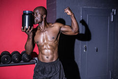 Young Bodybuilder showing his muscles while kissing a Bottle Royalty Free Stock Images
